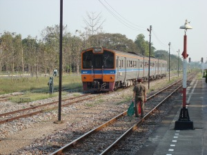 The stationmaster guided the arrival of train 407 from Nakhon Sawan.