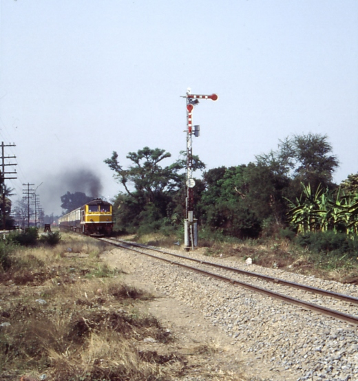Single track, semaphore and belching locomotive. Nothing new, as it was and still is. Chiang Mai March 1986